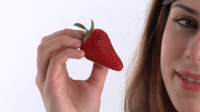 ECU, Young woman eating strawberry