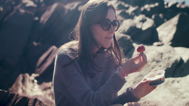 young woman eating strawberry with cream on rocky beach - kingsand video stock e b–roll