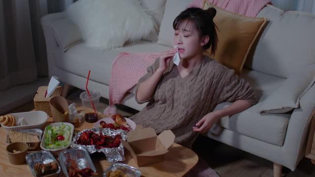 young woman eating take-out food at night,4k - 逸楽点の映像素材/bロール
