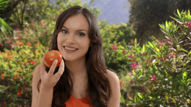 young woman eating tomato in garden - tomato stock videos & royalty-free footage