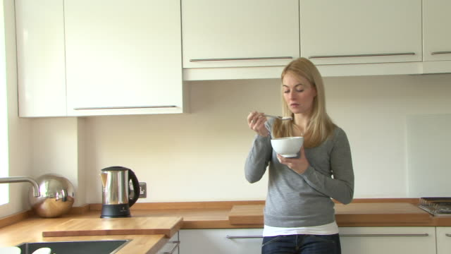 Young woman eating yoghurt in kitchen, UK