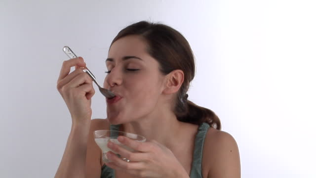 zi, ecu, young woman eating yoghurt with muesli - yoghurt stock videos and b-roll footage