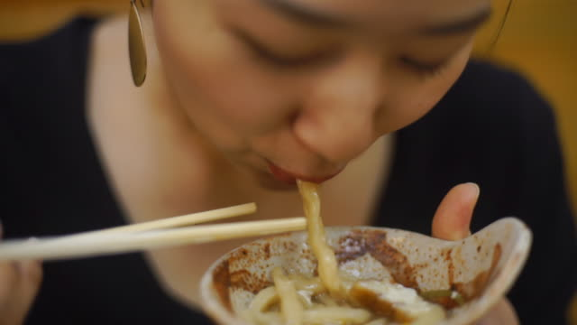 young woman eats udon noodles - japan - bacchette cinesi video stock e b–roll