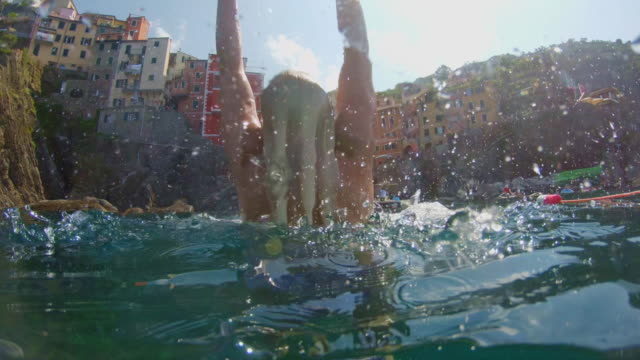 ms slow motion young woman emerging from underwater sea, cinque terre, italy - emergence stock videos & royalty-free footage