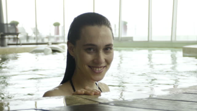 stockvideo's en b-roll-footage met young woman emerging from water in pool and smiling cheerfully - binnenbad