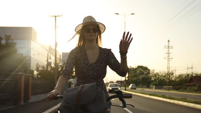la giovane donna si gode il giro in bicicletta all'aperto urbano al tramonto - salutarsi video stock e b–roll