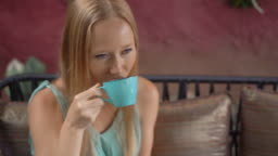 Young woman enjoy blue latte sitting in a beautiful cafe. Hot butterfly pea latte or blue spirulina latte. Slowmotion shot