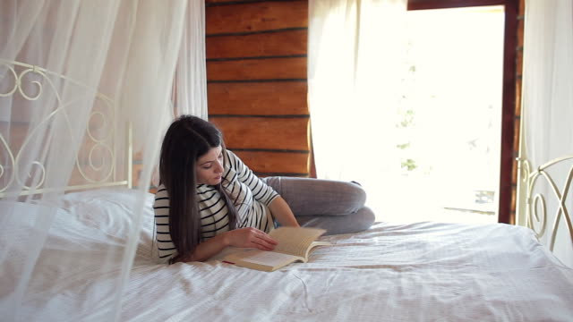 Young woman enjoying a book in bed.