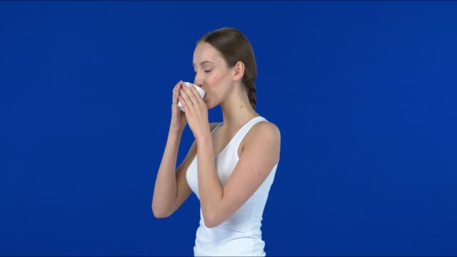 stockvideo's en b-roll-footage met jonge vrouw die van een kop koffie geniet. - natuurlijk haar