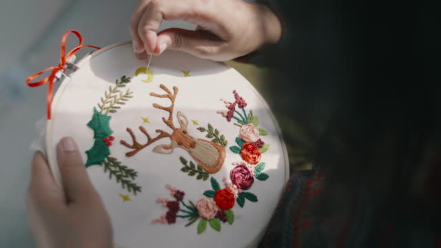 young woman enjoying cross-stitch for christmas in home. - embroidery stock videos & royalty-free footage