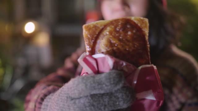 夜、路上でクロワッサン・タイヤキ(日本の魚の形をしたケーキ)を食べるのを楽しんでいる若い女性。 - カスタードクリーム点の映像素材/bロール