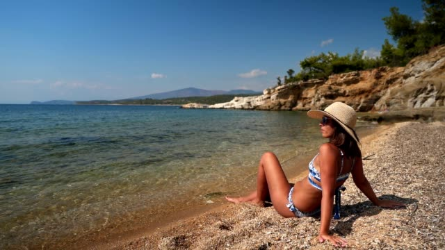 young woman enjoying holiday on the beach - sunbathing stock videos & royalty-free footage