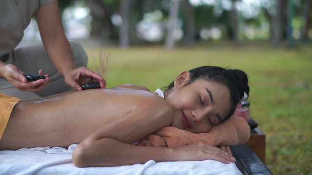 vídeos de stock, filmes e b-roll de young woman enjoying hot stone therapy at the spa - lastone therapy