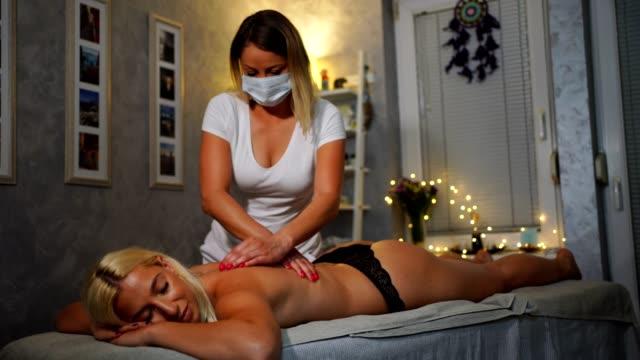 ung kvinna njuter av avkopplande massage - massage table bildbanksvideor och videomaterial från bakom kulisserna