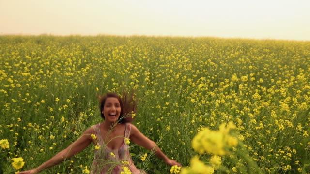 Young woman enjoying in the mustard field, Haryana, India