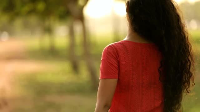 vídeos de stock, filmes e b-roll de young woman enjoying in the park, delhi, india - cabelo encaracolado