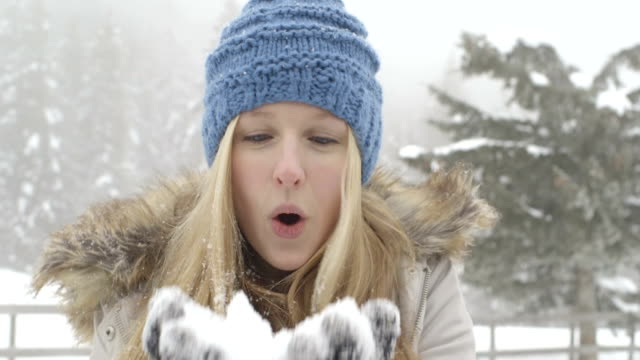 Young woman enjoying in winter with blowing snow