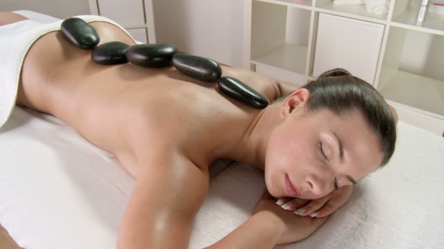 stockvideo's en b-roll-footage met hd crane: young woman enjoying lastone therapy - massage table