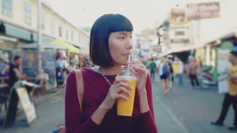 young woman enjoying mango juice in khao san road. bangkok, - mango fruit stock videos & royalty-free footage