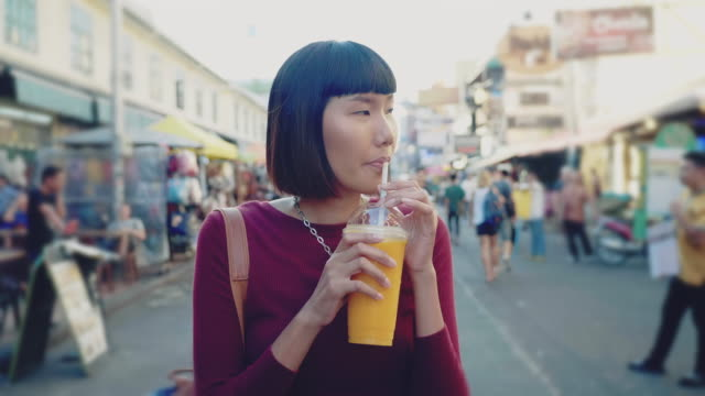 young woman enjoying mango juice in khao san road. bangkok, - smoothie stock videos & royalty-free footage