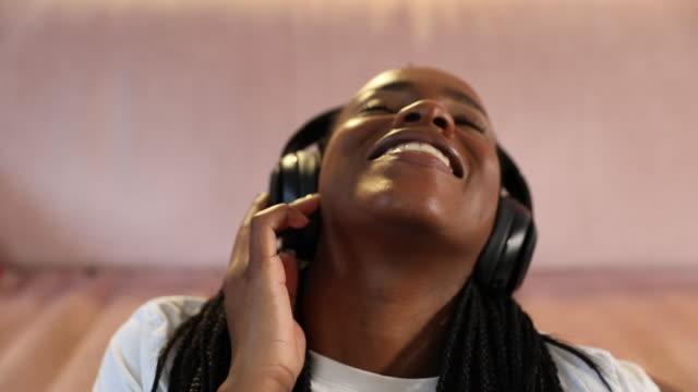 vídeos y material grabado en eventos de stock de joven disfrutando de la música en la sala de estar sentada en el suelo - escuchar