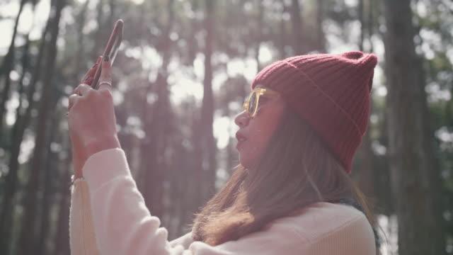vídeos y material grabado en eventos de stock de mujer joven disfrutar de la naturaleza en bosque andphotographing con un smartphone. - mirar hacia arriba