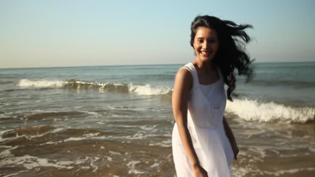 young woman enjoying on the beach  - ドレス点の映像素材/bロール
