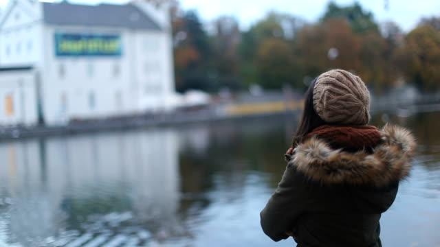 vidéos et rushes de jeune femme appréciant à prague par la rivière vltava - châle