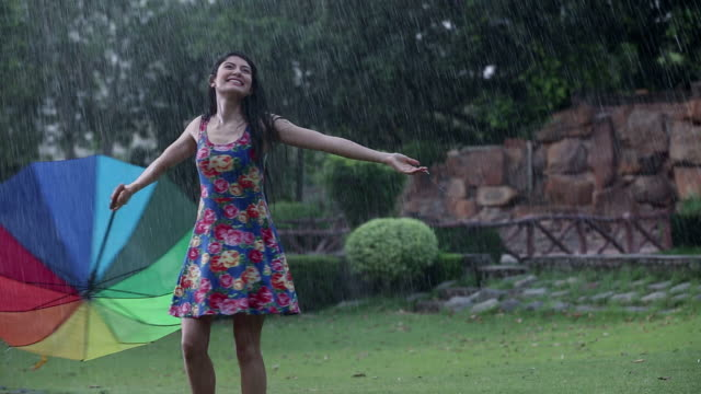 Young woman enjoying rain in the park