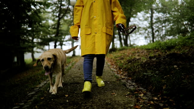Young woman enjoying rainy day with her dog