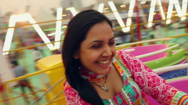 young woman enjoying rides, suraj kund fair, faridabad, haryana, india - haryana stock-videos und b-roll-filmmaterial
