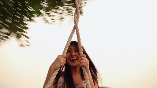 Young woman enjoying rope swing, Haryana, India