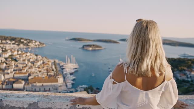 stockvideo's en b-roll-footage met ms jonge vrouw die van het toneel geniet adriatische overzees mening, de stad hvar, kroatië - kroatië
