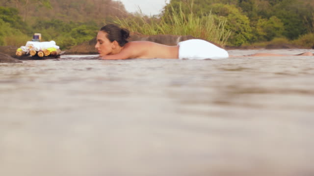 stockvideo's en b-roll-footage met young woman enjoying spa treatment at riverbank, kerala, india - in een handdoek gewikkeld