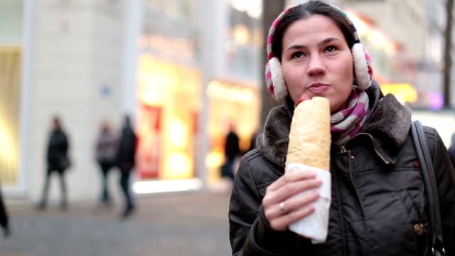 Ung kvinna njuter snabbmat på vintern
