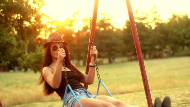 vídeos de stock, filmes e b-roll de jovem mulher desfrutar de verão do pôr-do-sol no balanço - swing