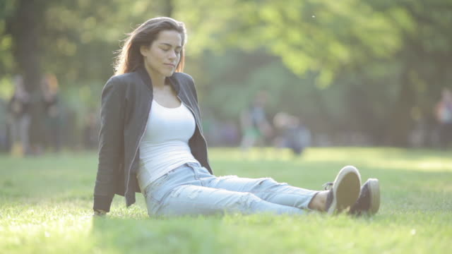 Young woman enjoying sunset sitting in grass, looking at cell phone in park in Berlin