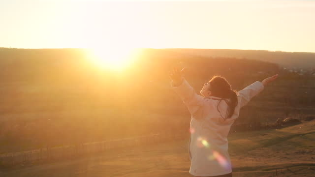 young woman enjoying the freedom in nature at sunset. - arms raised stock videos & royalty-free footage