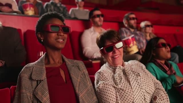 giovane donna che si gode i film - proiezione evento pubblicitario video stock e b–roll