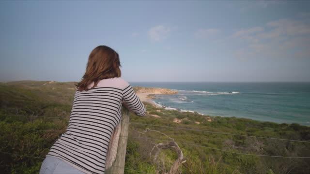 A young woman enjoying the sea views at Mornington Peninsula, Victoria, Australia