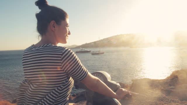 stockvideo's en b-roll-footage met jonge vrouw genieten van de zonsondergang op de motor-scooter. - mooie mensen
