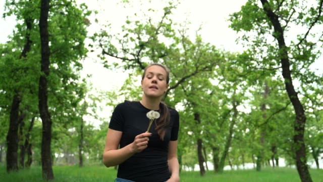 young woman enjoying walking in forest and blowing dandelion flowers - pollen stock videos & royalty-free footage