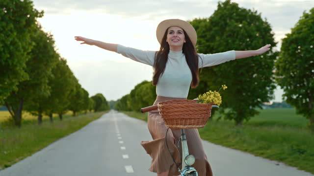 slow motion young woman enjoys riding a bicycle - treelined stock videos & royalty-free footage
