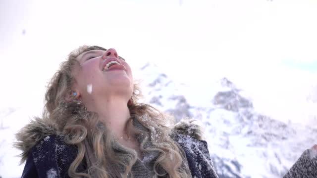Young woman enjoys snowflakes, mountain winter environment