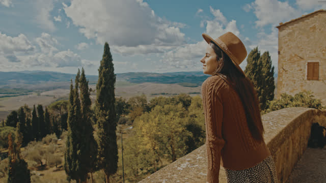 slo mo young woman enjoys the view from the city walls at pienza - escaping stock videos & royalty-free footage