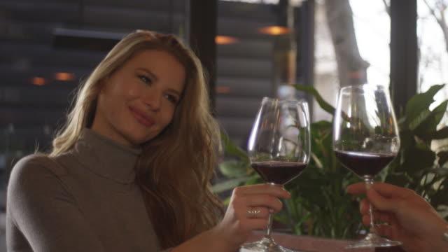 若い女性を楽しむとガラスの赤ワイン 4 k スローモーション - お食事デート点の映像素材/bロール
