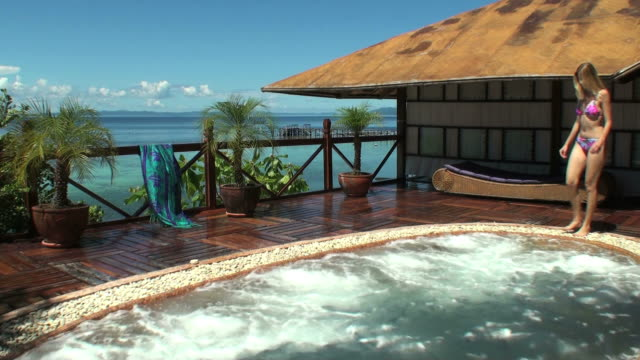 young woman entering a spa overlooking the ocean and relaxing - spa stock videos & royalty-free footage