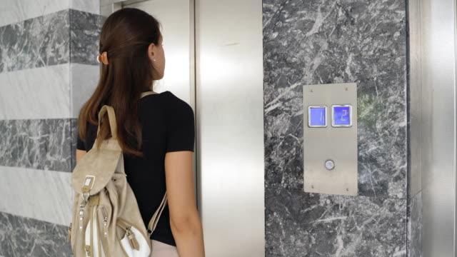vídeos y material grabado en eventos de stock de mujer joven que entra en ascensor en el piso duodécimo - esperar