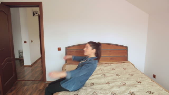 young woman entering in her room. - lying on back stock videos and b-roll footage