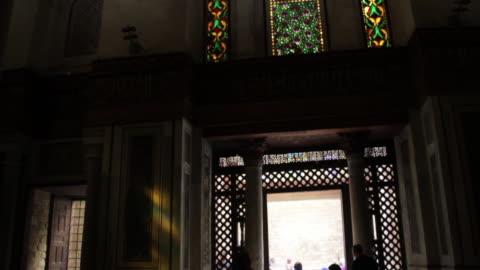 vídeos de stock, filmes e b-roll de young woman enters a building in coptic cairo, tilt up. - ponto turístico local